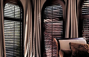 Arched window coverings could be challenging, shutters maybe the best soultion